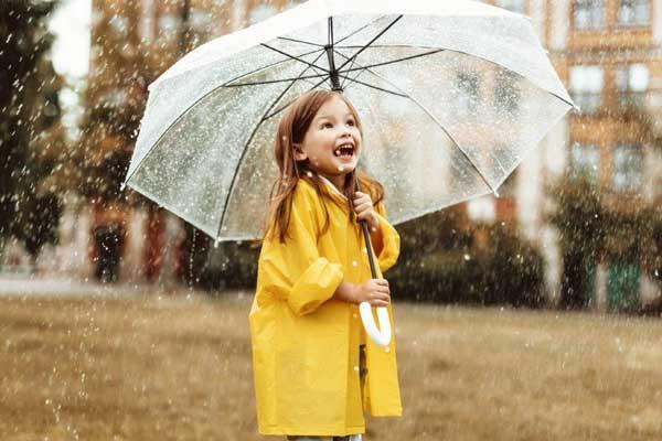 mädchen in gelbem regenmantel